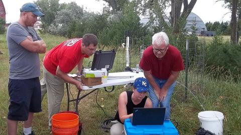 People working together in field and looking at laptop