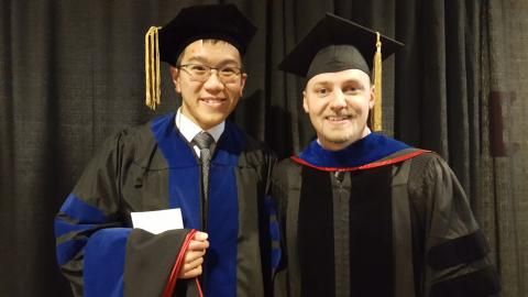 Two men standing together after receiving diploma